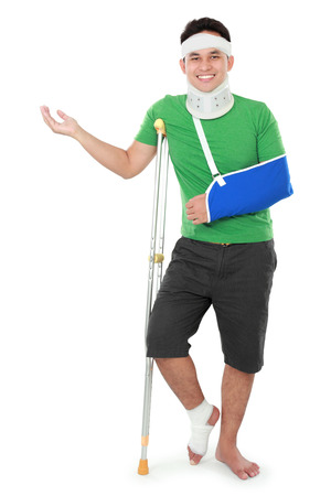 copyspace: portrait of a smiling male with broken arm and foot using crutch presenting to copyspace isolated on white background