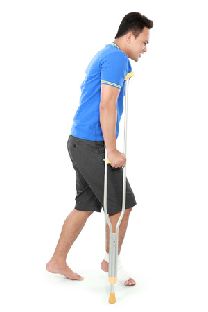 crutch: Full length portrait of a male with broken foot using crutch trying to walk isolated on white background