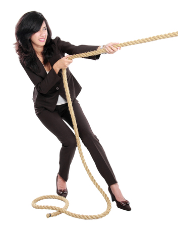 woman hard working: Business competition. Young business woman pulling a rope isolated on white background