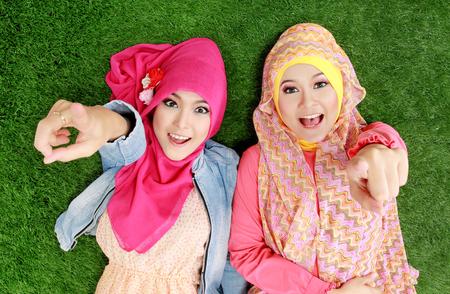 草の上に横たわる 2 つの美しい幸せなイスラム教徒の女性をクローズ アップの肖像画 写真素材
