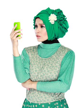 portrait of asian woman with head scarf holding mobile phone. confuse or shocked expression