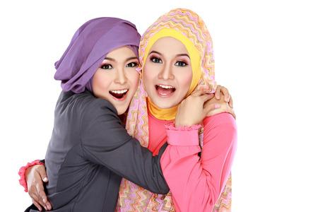 함께 흰색 배경 위에 고립 된 두 아름다운 이슬람교 여자 재미의 초상화 스톡 콘텐츠