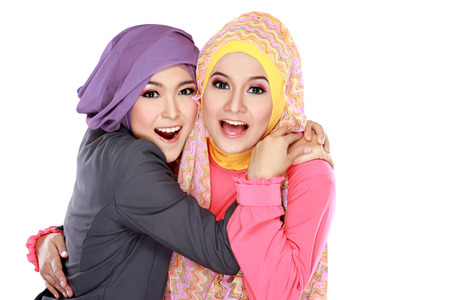 Portrait of two beautiful moslem woman having fun together isolated over white background