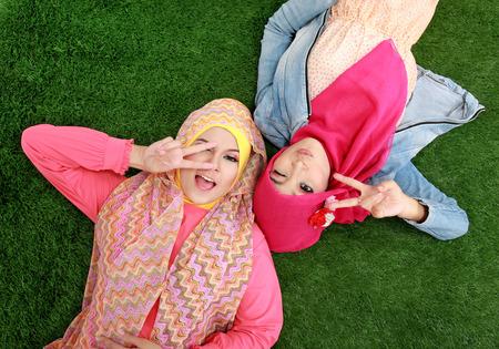 Portrait of close up two beautiful happy muslim woman lying on grass Stock Photo - 25935124