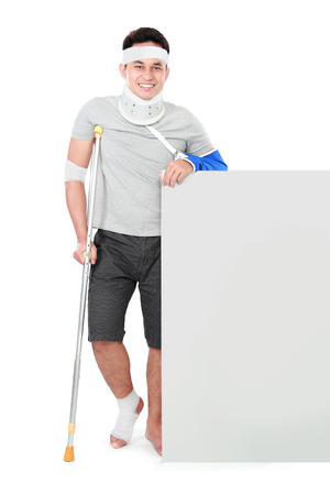 injure: portrait of a smiling male with broken arm and foot using crutch presenting to copyspace isolated on white background