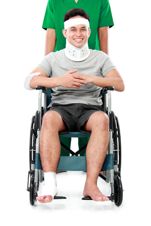 injured person: portrait of a smiling male with broken arm and foot using wheel chair isolated on white background