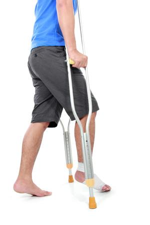 pies masculinos: retrato de una fractura en el pie usando muletas tratando de caminar aislado en el fondo blanco