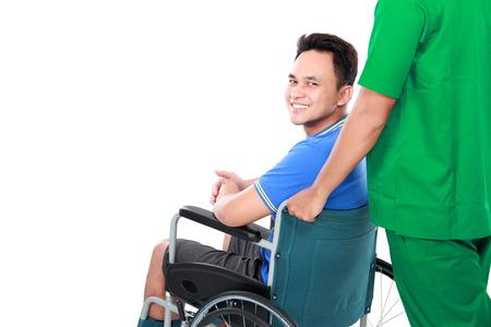骨折した腕と足が車椅子を使用して笑みを浮かべて男性の肖像画。外科医に助けられ