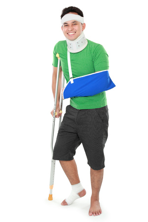 injure: Full length portrait of a smiling male with broken arm and foot using crutch isolated on white background Stock Photo