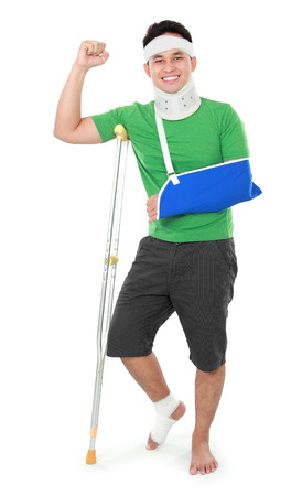 broken foot: Full length portrait of a smiling male with broken arm and foot using crutch isolated on white background Stock Photo