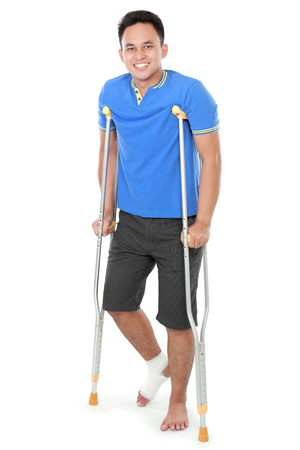 crutch: Full length portrait of a smiling male with broken leg using crutch isolated on white background