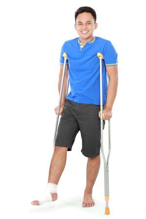 pierna rota: Retrato de cuerpo entero de un hombre que sonríe con la pierna rota usando muletas aislados en fondo blanco