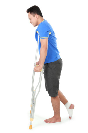 crutch: Full length portrait of a male with broken leg using crutch trying to walk isolated on white background