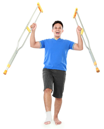 crutch: Full length portrait of a happy smiling male with broken foot using crutch isolated on white background Stock Photo