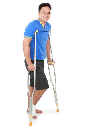 crutch: Full length portrait of a smiling male with broken foot using crutch isolated on white background Stock Photo