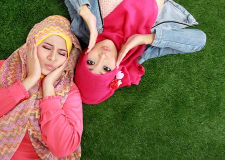 Portrait of close up two beautiful happy muslim woman lying on grass photo