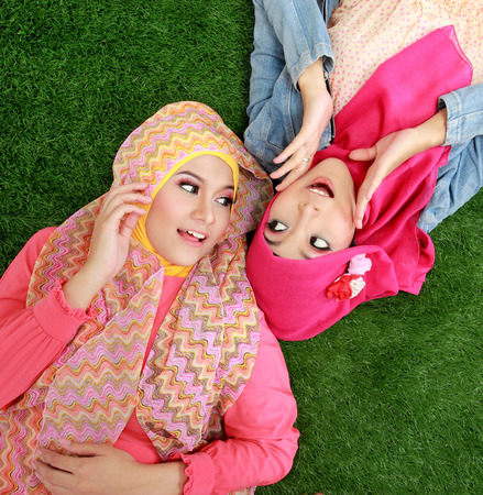 Portrait of close up two beautiful happy muslim woman lying on grass photo