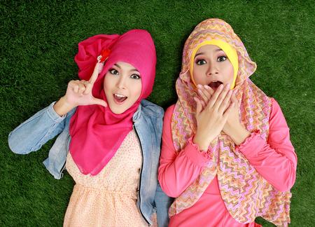 cerrar: Retrato de primer plano de dos hermosa mujer musulmán feliz tirado en la hierba