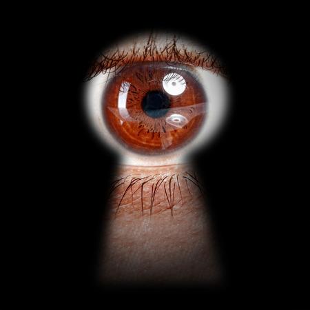 eye hole: eye peeking through a keyhole concept for curiosity, stalker, surveillance and security