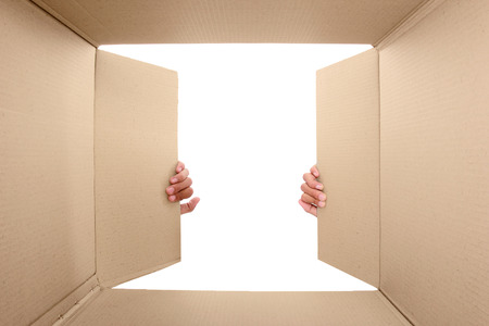 corrugated box: hand open cardboard box. potrait from inside the box Stock Photo