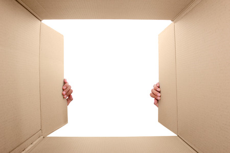 hand open cardboard box. potrait from inside the box Stock Photo