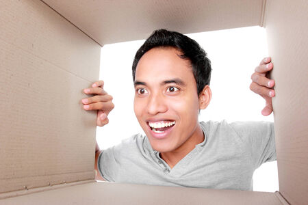 corrugated box: portrait of a man looking for something inside box Stock Photo