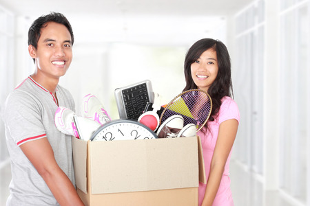 man and woman with their stuff inside the cardboard box ready to move. moving day concept
