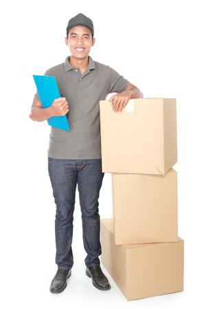 Smiling young delivery man with cardbox package isolated on white background photo