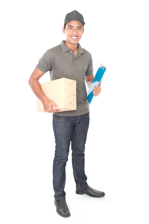 Smiling young delivery man holding and carrying a cardboard box package isolated on white background photo