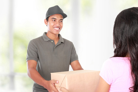 Receiving: Woman receiving a package at home from a delivery guy Stock Photo