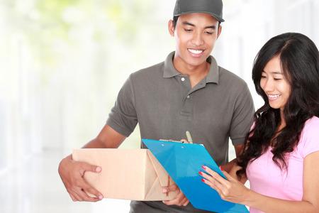 Frau, die eine Paket zu Hause aus einer Lieferung Mann Standard-Bild - 26764144