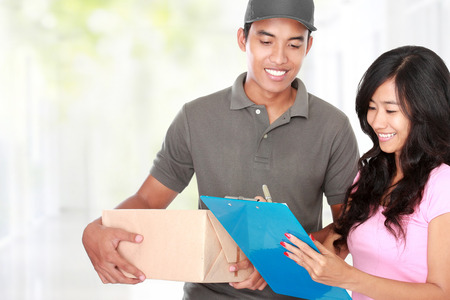 send parcel: Woman receiving a package at home from a delivery guy Stock Photo