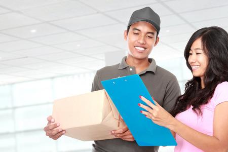 pakiety: Portret mężczyzny dostawy wysyłającego pakiet do młodej kobiety