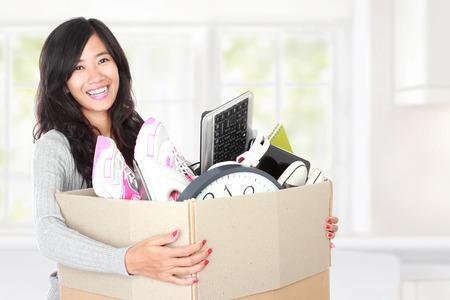 彼女のものに移動する準備ができている段ボール箱の中の女性。移動日の概念