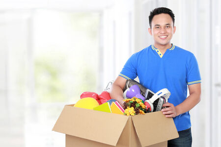 Smiling young man with cardboard box. moving day concept Stock Photo