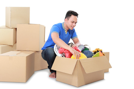 Smiling young man with cardboard box. moving day concept photo