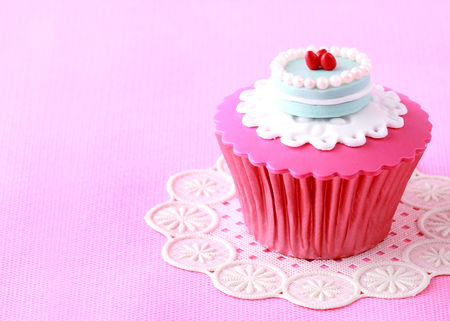 sugar paste: sweet cupcakes decorated with sugar paste and cream Stock Photo