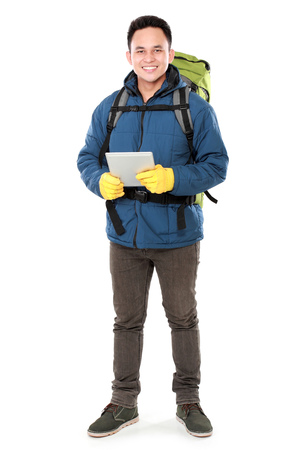 Full length portrait of a smiling male hiker with backpack using tablet computer isolated on white background photo
