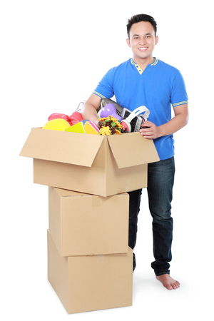 moving box: Smiling young man with cardboard box. moving day concept Stock Photo