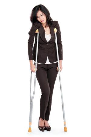 白い背景で隔離の松葉杖を持つ若いビジネス女性