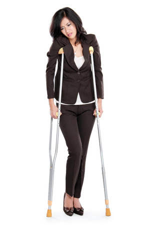 broken back: Young business woman with crutches, isolated on white background