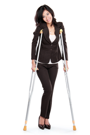 Young business woman with crutches, isolated on white background