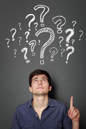 punto interrogativo: giovane uomo con punto interrogativo su uno sfondo grigio