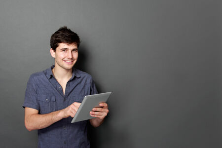 young male smiling using digital tablet against gray background photo