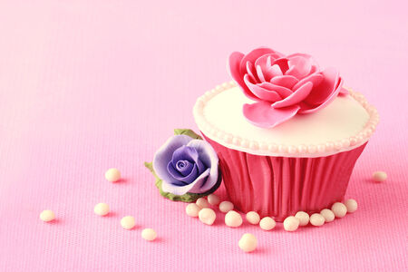 Sweet Cupcake with flower decoration in pink Stock Photo - 26258501
