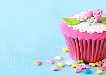 Sweet Cupcake with flower decoration in pink Stock Photo - 26258385