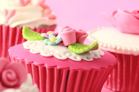 sweet cupcakes decorated with sugar paste and cream photo