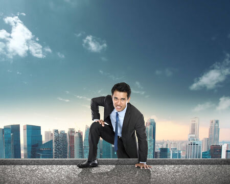 struggling: portrait of businessman struggling on climbing to the top of the building Stock Photo