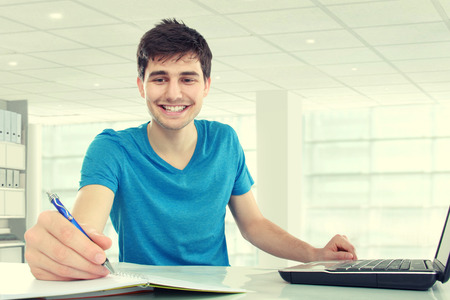 handsome young student happy about research results from the internet photo