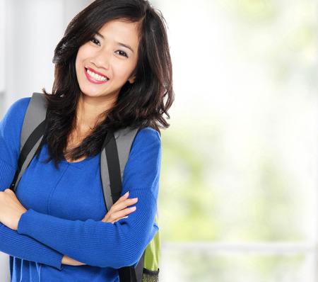 portrait of Young female happy student carrying bag at university photo